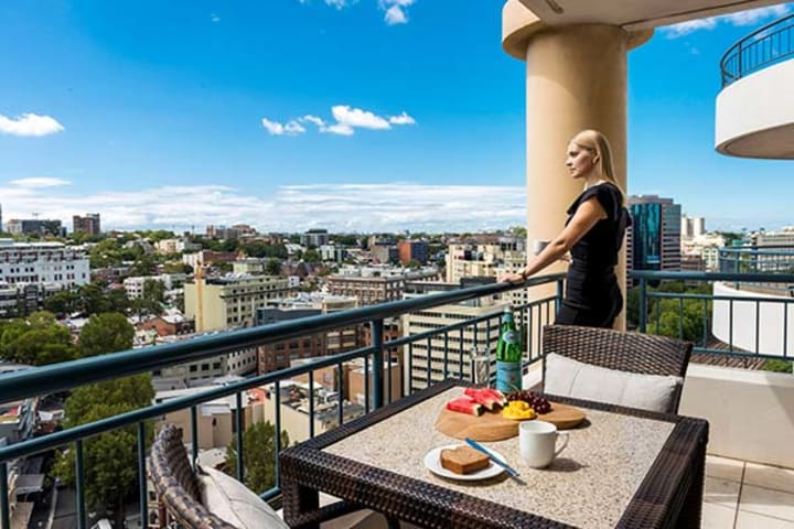 hotel visitor on balcony with breakfast on table and views of Sydney city in background