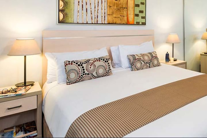 studio hotel accommodation in Sydney with queen-size bed, large wardrobe and full length mirror for guests