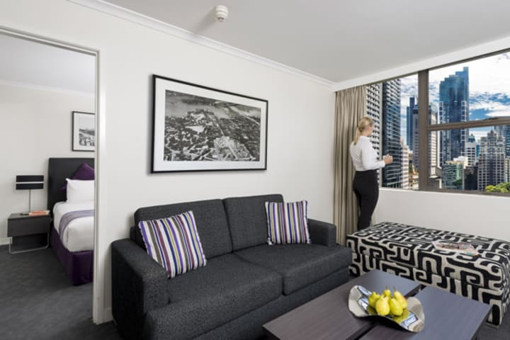 corporate traveller on business trip looking out of window of Hyde Park hotel 1 bedroom executive apartment at Oaks Hyde Park Plaza hotel in Sydney