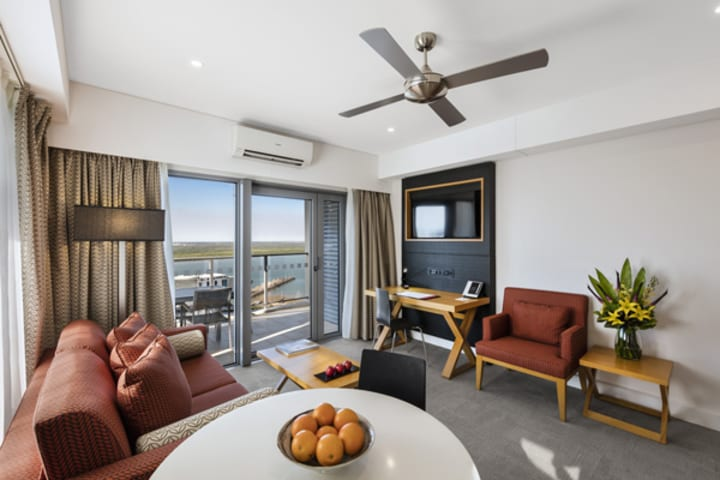 modern living room in 1 bedroom hotel apartment in Darwin hotels with TV, ceiling fan, air con and balcony at Oaks Elan Darwin in Northern Territory