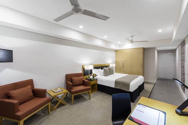 Darwin hotel room with air conditioner, ceiling fan, queen size bed and views of harbour