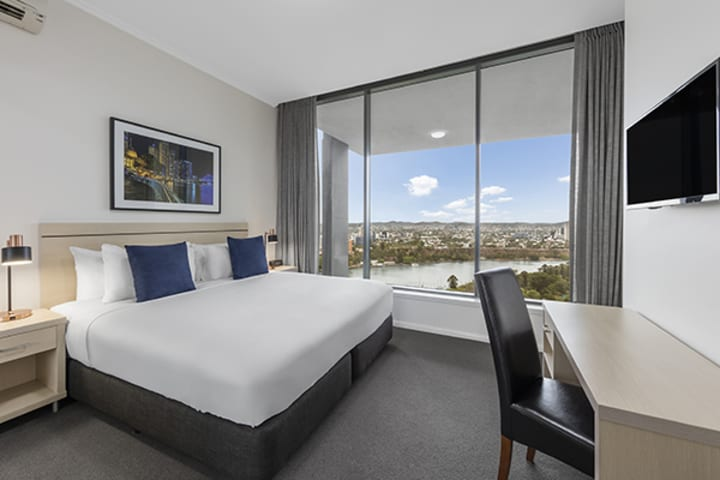 king-sized bedroom with nice brisbane city view and a study desk at oaks 212 margaret 4 bedroom brisbane hotel