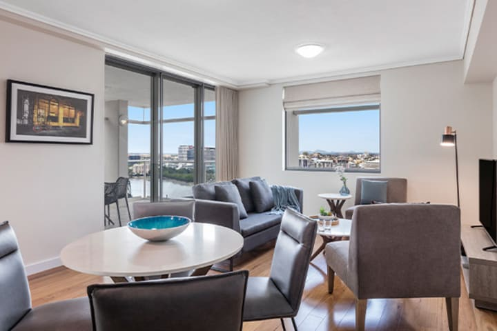 Spacious living and dining room connected to a spacious balcony at Oaks Brisbane Casino Tower Suites one bedroom executive