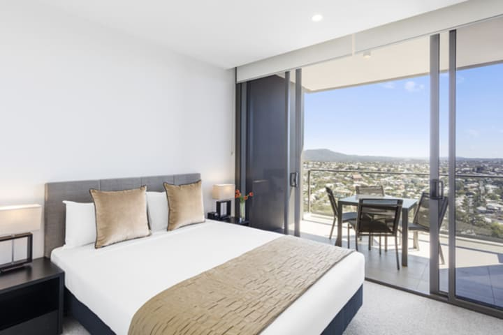 2 bedroom apartment with balcony, tables and chairs with views of Brisbane River at The Milton hotel near train station