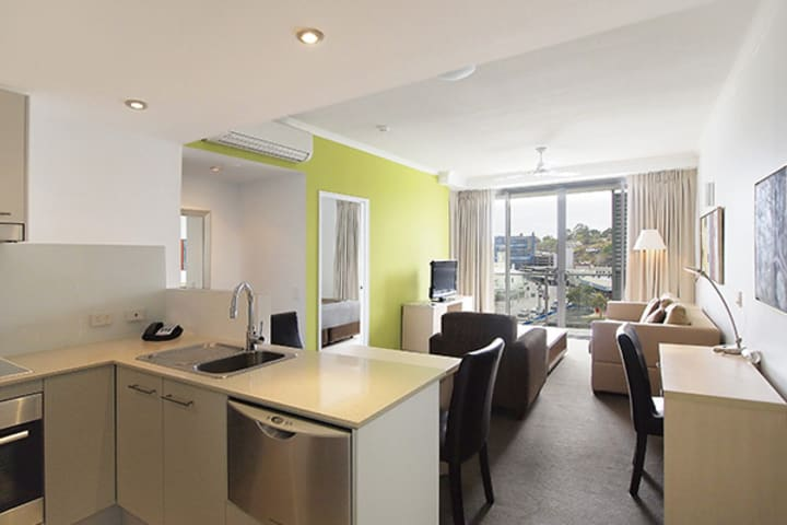 open plan living room and kitchenette area with air con and wi-fi in Townsville holiday apartments at Oaks Gateway Suites hotel in South Townsville