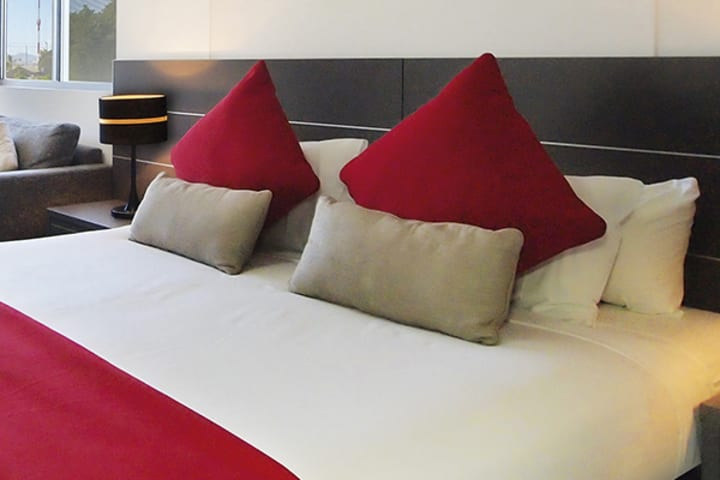Townsville hotels soft pillows on comfortable, clean queen size bed in 2 bedroom apartment at Oaks Metropole Hotel in South Townsville