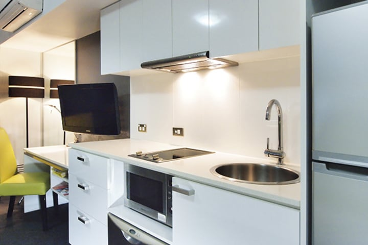 Hotels Townsville kitchen with large fridge and microwave in air conditioned studio apartment at Oaks Metropole Hotel in Townsville
