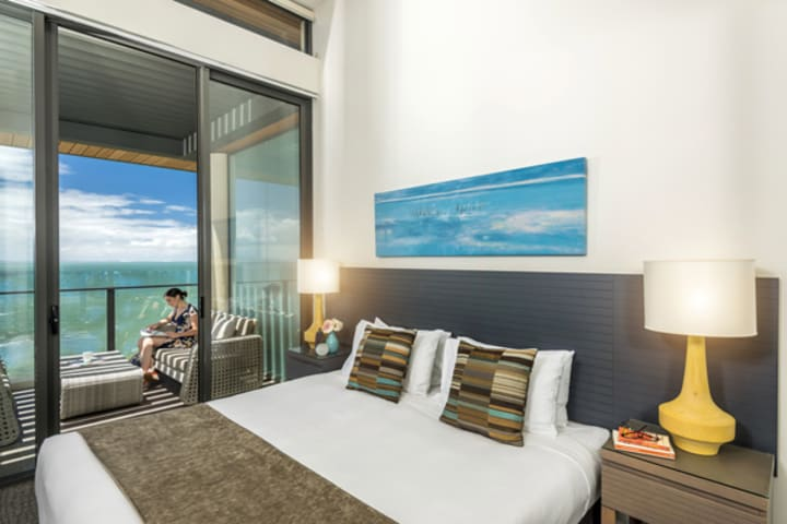 comfortable queen size bed in master bedroom of 3 bedroom apartment with private balcony at Mon Komo Hotel in Redcliffe