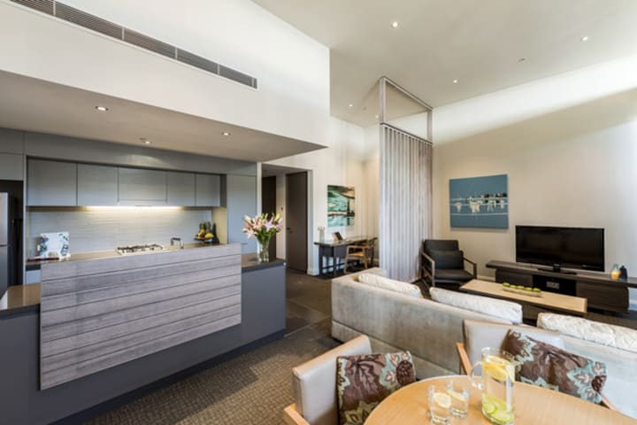 open plan living room and kitchen area with aircon, wi-fi and TV with Foxtel at Mon Komo Hotel in Redcliffe