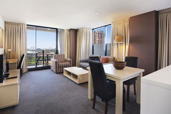 accommodation in adelaide city with air conditioned 2 bedroom apartment with table, chairs, couches, Wi-Fi access and private balcony outside with view of Adelaide Oval across the river