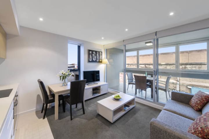 large living room with plenty of light, modern furniture, TV and private balcony in 2 bedroom apartment at iStay Precinct hotel in Adelaide city