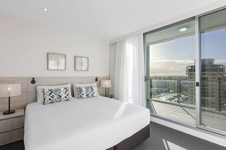 Glenelg accommodation with big comfortable bed with clean white sheets in air conditioned 1 bedroom apartment with private balcony outside at Oaks Liberty Towers hotel in Glenelg