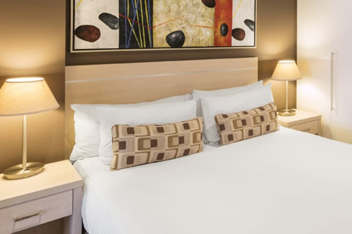 Best hotels Glenelg close up of colourful pillows on clean white bed sheets on queen size bed with side tables and picture on wall in air conditioned 1 bedroom apartment at Oaks Plaza Pier hotel in Glenelg, South Australia