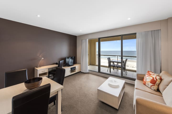 spacious living room with air con and wi-fi access leading out to big beachfront private balcony in 1 bedroom apartment at Oaks Plaza Pier hotel in Glenelg, South Australia