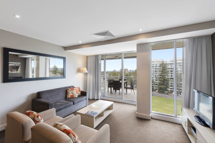 spacious living room with comfortable couches, free Wi-Fi access and private balcony outside 2 Bedroom Apartment at Oaks Plaza Pier hotel in Glenelg, South Australia