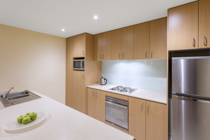 spacious kitchen with microwave, big fridge, freezer, toaster and dishwasher in 2 bedroom apartment at Oaks on Lonsdale hotel, Melbourne city, Victoria, Australia