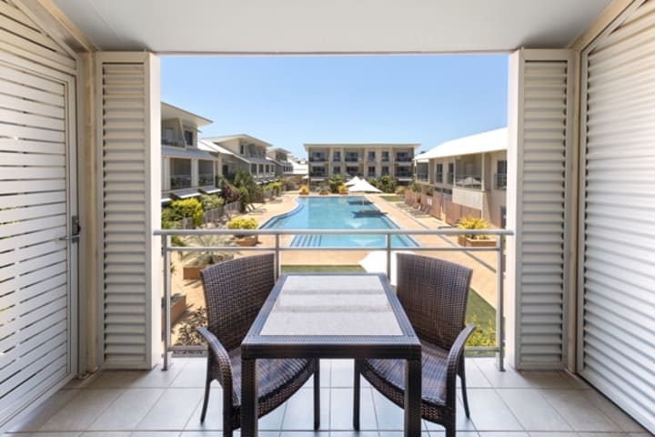 view of large swimming pool from private balcony with table and chairs outside 1 bedroom apartment at Oaks Broome hotel, Western Australia