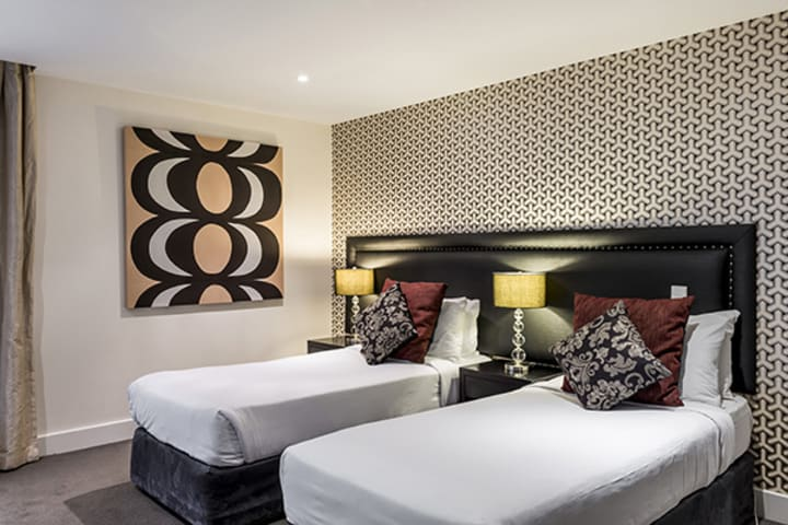 two single beds for kids in big Hotel Room holiday apartment near snowboarding and bungy jumping activities in Queenstown, New Zealand