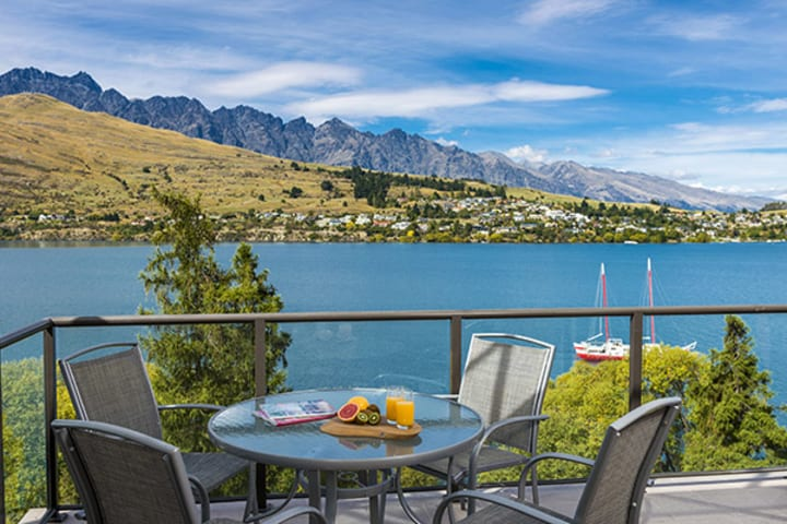 vegetarian breakfast options on table on private balcony of 1 Bedroom Apartment with views of boats and tourists on holiday enjoying activities on Lake Wakatipu in Queenstown, New Zealand