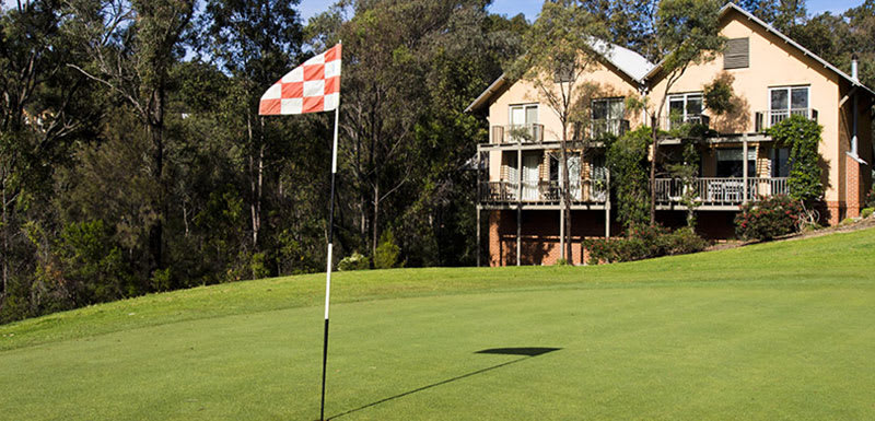 golf green with red and white flag pole in hunter valley