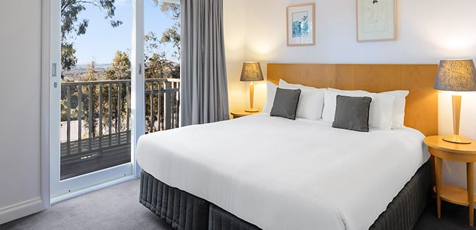 Hunter Valley resort bedroom with king size bed near window looking out over forest and golf course