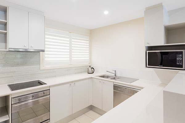 clean kitchen area in 1 bedroom apartment with microwave oven and stove top