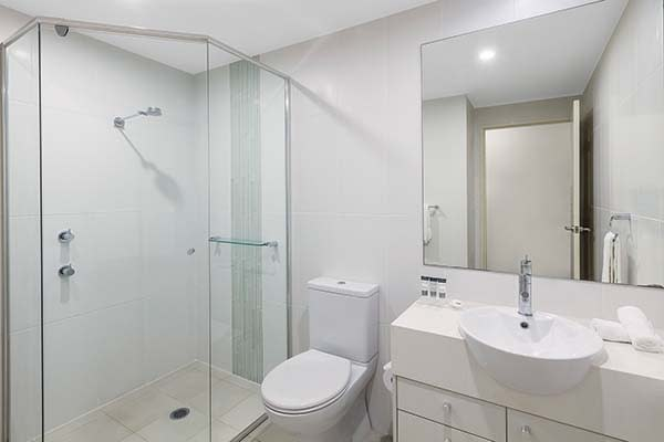 bathroom with toilet and shower at oaks pacific blue resort hotel in port stephens