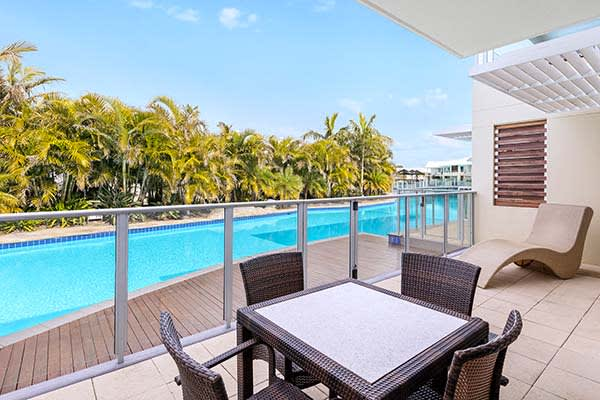 Port Stephens resorts courtyard with table reclining chair and blue skies at oaks pacific blue resort hotel NSW