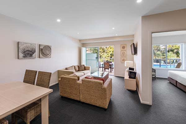 large living room adjacent to hotel bedroom at port stephens hotel resort with swimming pool in background