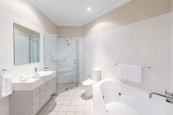 large bathroom with bathtub at port stephens hotel resort near karuah river