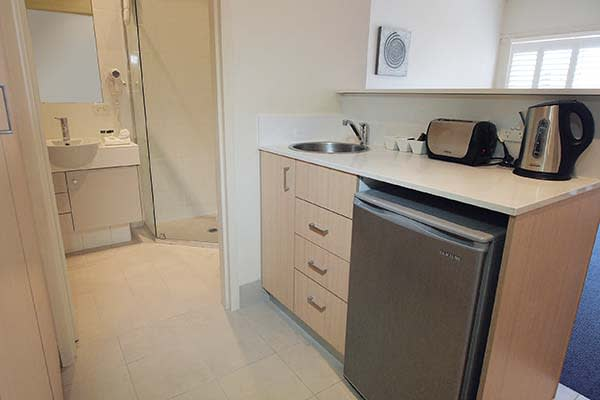 kitchenette area with fridge kettle and toaster at oaks pacific blue resort