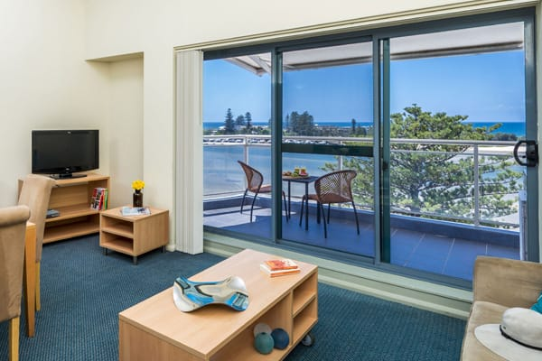 hotel apartment living room with television and balcony with views of The Entrance nsw