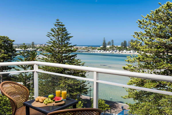 hotel balcony with breakfast on table and views of Tuggerah Lake