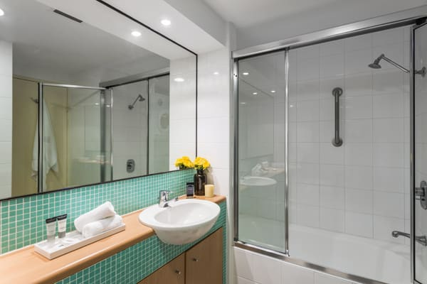 en suite bathroom in studio ocean view apartment with mirror and shower