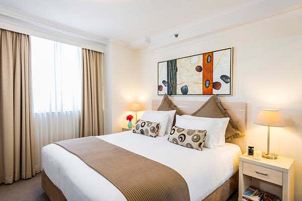 1 bedroom apartment in Sydney CBD with large bed, window and side tables on either side of queen size bed