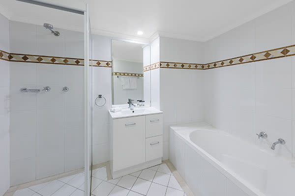 clean bathroom with a bathtub and a walk-in shower at one bedroom apartment of oaks on castlereagh sydney hotel