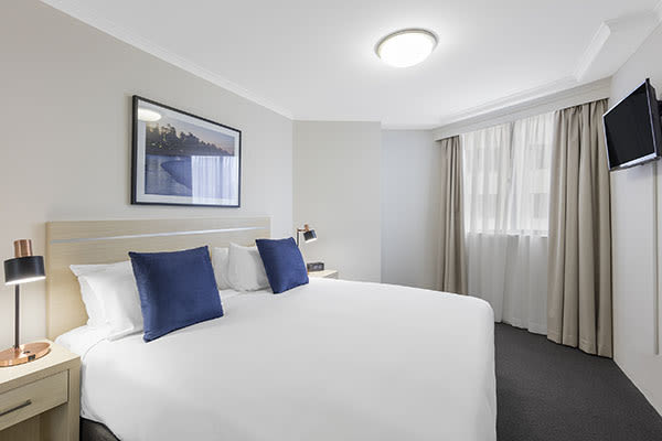 king-sized bed and lamps supporting USB charging in the one bedroom apartment of oaks on castlereagh sydney hotel