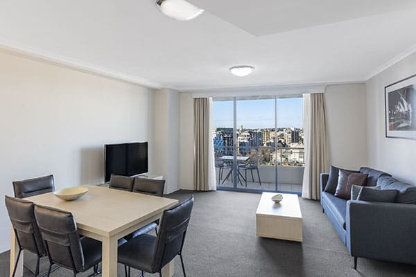 sofa, dining table and flat TV in a spacious living room connected to a balcony with city view at one bedroom apartment of oaks on castlereagh sydney hotel