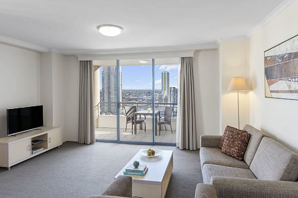 spacious living room with a sofa, a table and flat tv, connected to a balcony with city view at one bedroom apartment of oaks on castlereagh sydney hotel