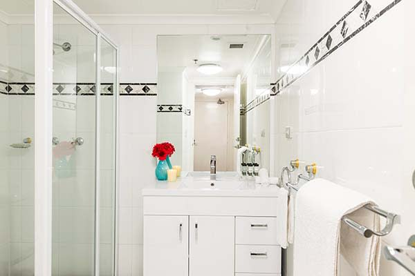 hotel bathroom with fresh towels, shower, storage space and large mirror
