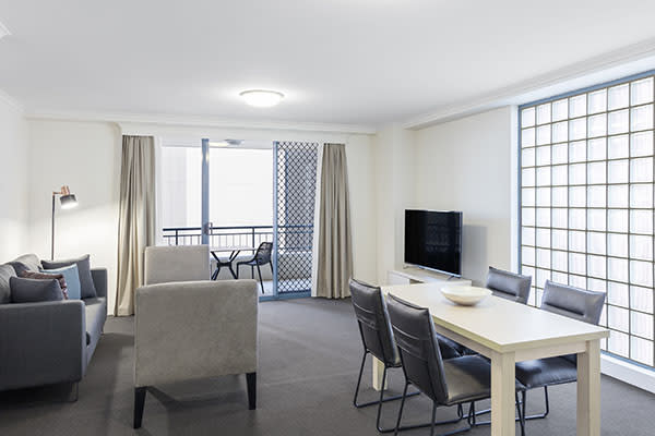 Spacious living room with modern furniture, connected to a balcony at two bedroom apartment of oaks on castlereagh sydney hotel