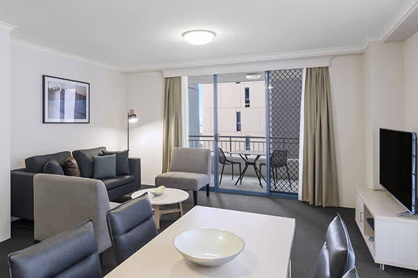 bright and Spacious living room with modern furniture, connected to a balcony at two bedroom apartment of oaks on castlereagh sydney hotel