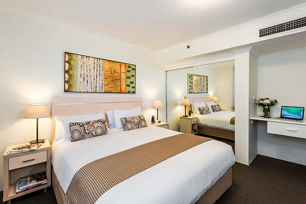 master bedroom at oaks on castlereagh hotel with large cupboards and work space for business travellers visiting Sydney