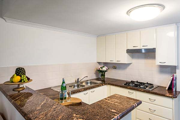 open plan kitchen with large bench tops, cutting board and cook top for cooking meals
