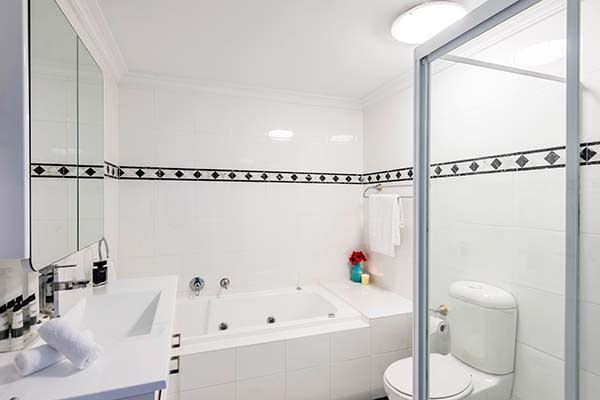en suite bathroom in 3 bedroom hotel apartment at Oaks on Castlereagh in Sydney city centre with shower, toilet and bath