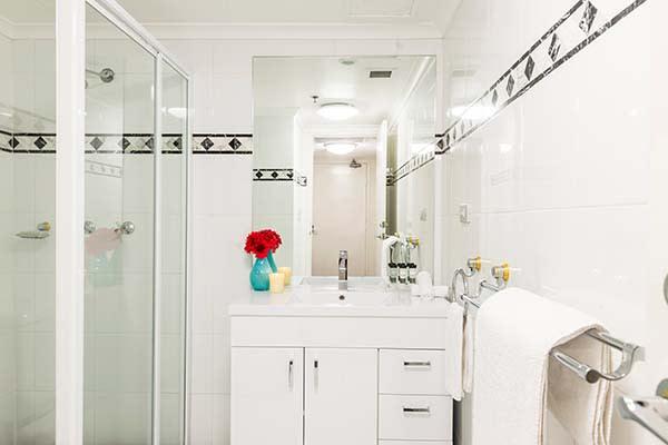 en suite bathroom with fresh towels, big shower and vanity cabinet for hotel visitors in Sydney CBD