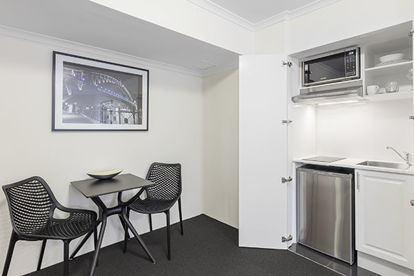 kitchenette, dining table, microwave and dishwasher at studio city bedroom of oaks on castlereagh sydney central hotel