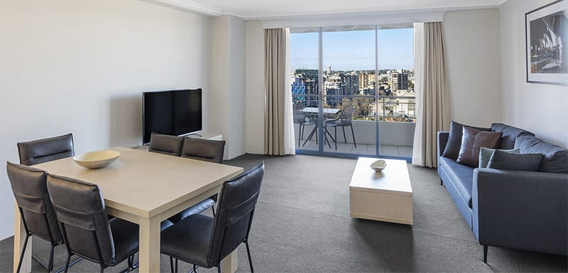 spacious living room connected to the balcony with city view at oaks on castlereagh sydney hotel