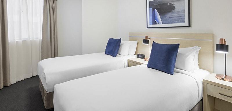two single beds and lamps with usb charging function on both sides of the stand in the two bedroom at oaks on castlereagh sydney hotel
