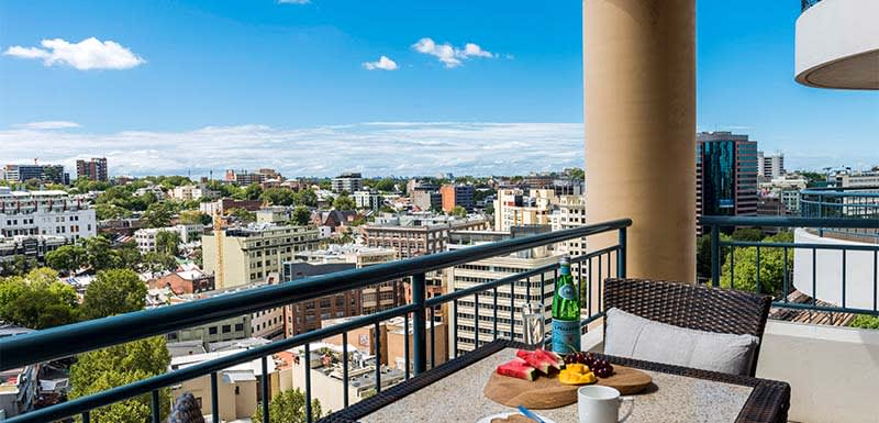 Balcony with hotel breakfast on table and great views of Sydney city